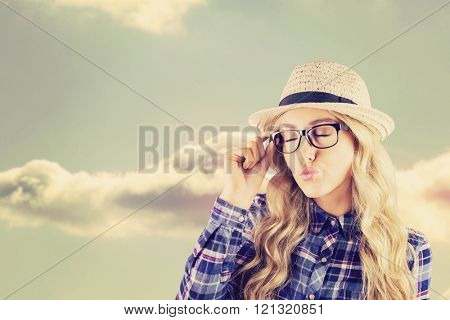 Gorgeous blonde hipster sending air kiss against bright blue sky with cloud