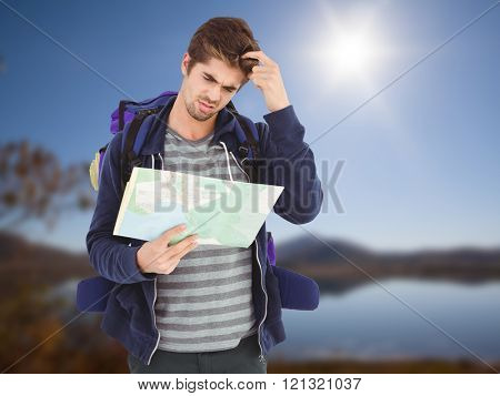 Man scratching head while looking in map against lake