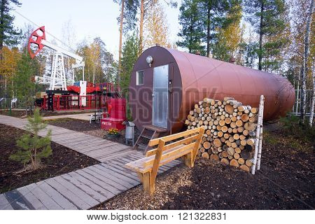 Oil rocking and residential trailer-a barrel with a stock of firewood in the forest.