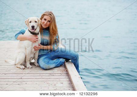 Hermosa chica con su perro en el muelle cerca mar