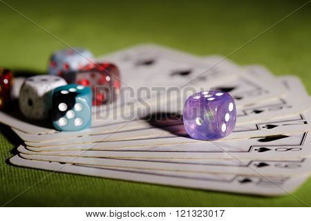 Purple Dice On Used Playing Cards