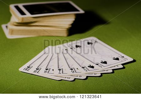 Used Playing Cards On Green Carpet