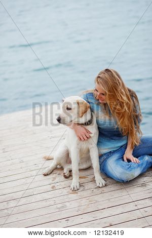 Beautiful girl with her dog on berth near sea