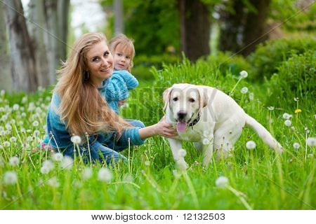 Beautiful woman with little girl and dog outdoors