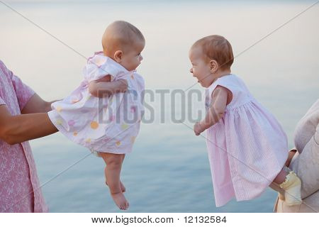 Sweet infant twins on parent's hands over sea