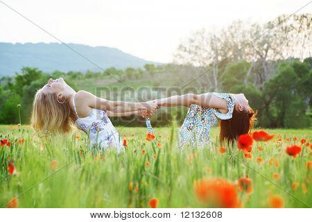 Posing two girls in poppy field on sunset