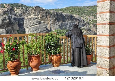 Nun enjoys a beautiful view of the mountains from the balcony of a monastery in Meteora. Greece.