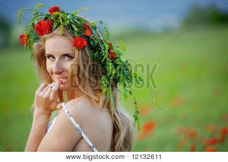Pretty woman wearing floral wreath on blurred fresh grass background