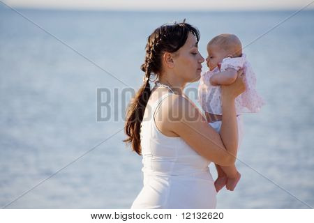 Mother holding her infant child over sea