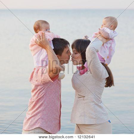 Jovens pais com crianças beijando sobre mar