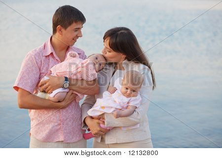 Happy young family with infant kids over sea