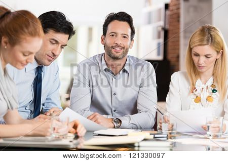 Young businessman looking at camera with colleagues in office. Portrait of proud smiling business man sitting with his colleagues during a meeting. Smiling businessman with executives working.
