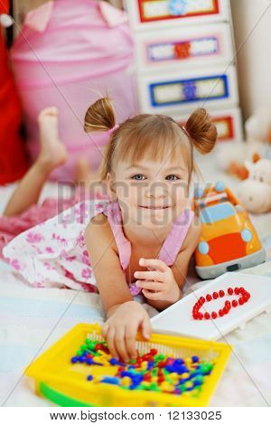 Little girl playing with mosaic in her nursery