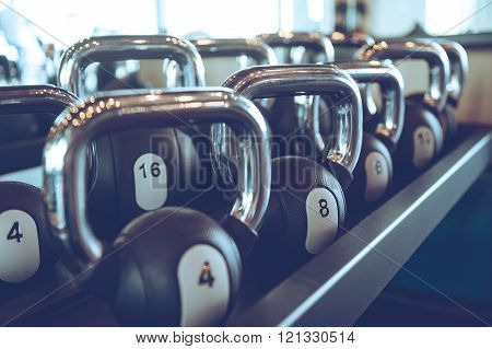 Kettle bells. Close-up of kettle bells lying on shelf at gym