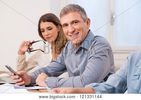 Portrait of mature business man looking at camera during a meeting. Senior man using mobile phone while looking at camera and smiling. Portrait of executive businessman with his colleaugues.