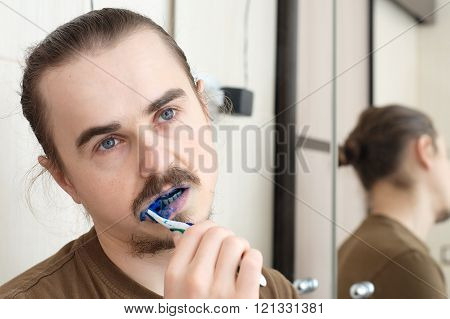 Confused Man Cleaning His Teeth With Blue Colour
