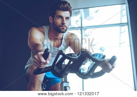 Confident cycler. Low angle view of young man in sportswear cycling at gym
