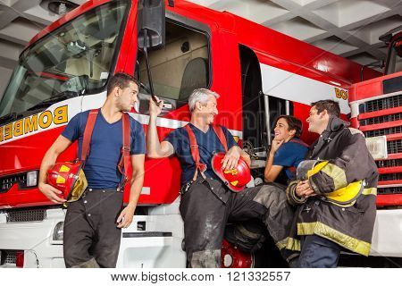 Happy Firefighters Conversing While Leaning On Trucks
