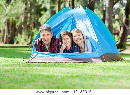 Family Relaxing In Tent At Park