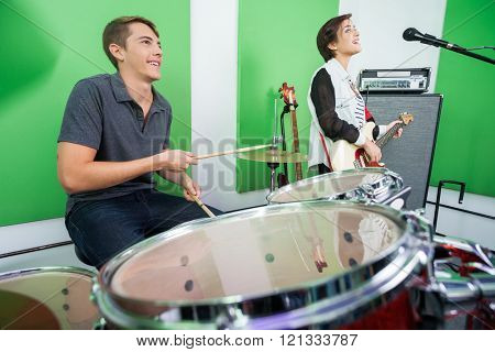 Drummer And Singer Performing In Recording Studio