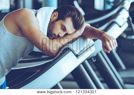 Cannot run anymore. Side view of young man in sportswear looking exhausted while leaning on treadmill at gym