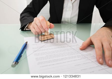 Businesswoman Hand Using Stamper On Document