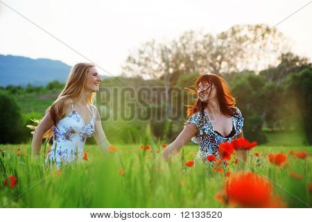 Running two girls in poppy field on sunset