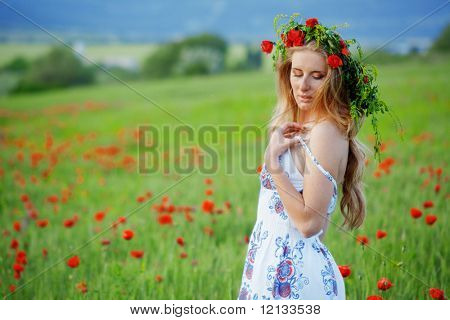 Beautiful girl wearing floral wreath over blurred fresh grass and flowers