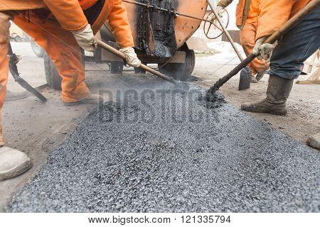 Road workers laid asphalt, repairing the road