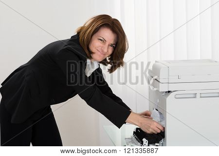 Businesswoman Removing Paper Stuck In Photocopy Machine