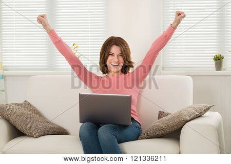 Excited Woman Sitting On Sofa With Laptop