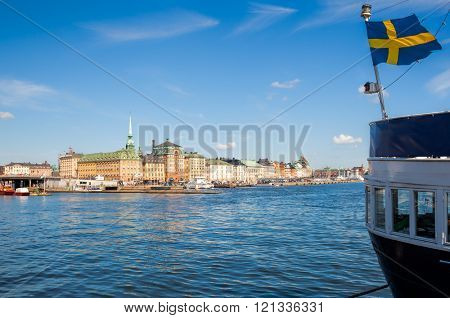 View of the harbour of Skeppsbron, the eastern waterfront of Gamla stan (the old town of Stockholm), with waving Swedish flag on moored ship in foreground