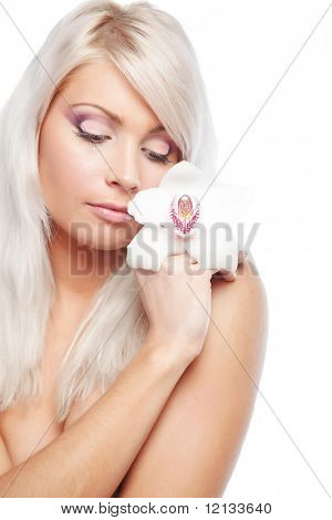 Studio portrait of beautiful blond woman with orchid and professional makeup