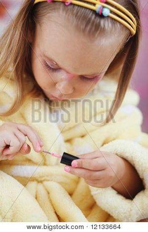 Little girl playing with cosmetics of her mother at home