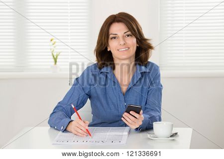 Woman Reading Classifieds On Newspaper