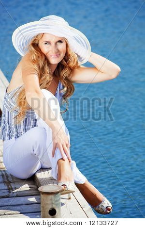Beautiful young girl spend her vacation on berth near sea in summer day