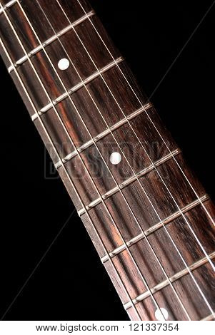 Electric guitar fretboard with strings over black background