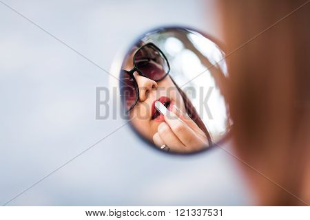 Woman Applying Lips Make-up With The Help Of Her Scooter Mirror. Defocused Background.