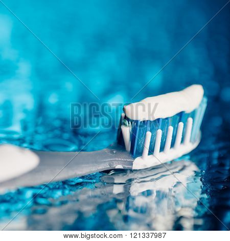 toothbrush on blue background with water drops