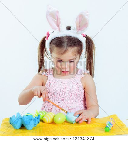 Preschooler with Easter bunny ears on is painting eggs