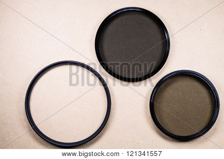 Photographic camera equipment lens filter on wodden background