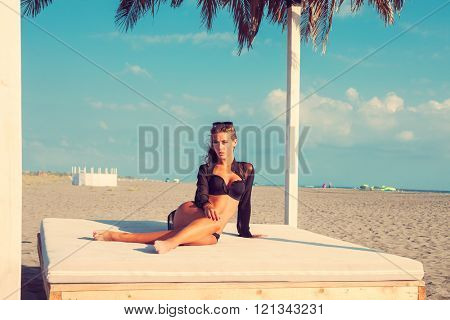 attractive tanned young woman in black bikini and shirt on beach bed at sand sea  beach, summer sunny day full body shot