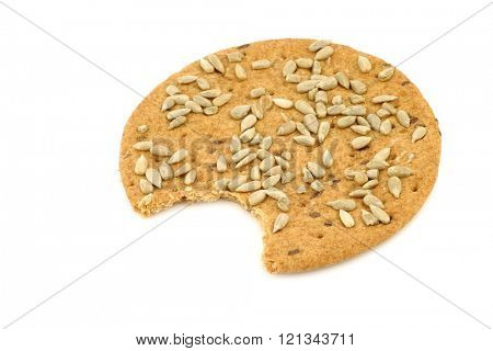 crispy spelt crackers with sunflower seeds with a bite missing on a white background