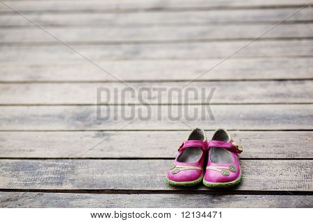 Kid girl small shoes leaved on wood