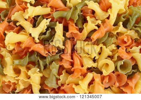 Food background - uncooked three-colored Campanelle durum wheat pasta with spinach and tomato