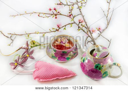 Heart-shaped pillow, blooming almond tree branch, tea-cup and tea-pot