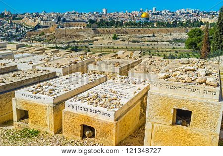 JERUSALEM ISRAEL - FEBRUARY 16 2016: The visitors of Jewish cemetery put the stones on the graves according to the ancient traditions on February 16 in Jerusalem.