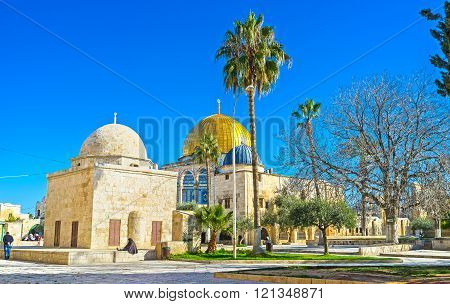 JERUSALEM ISRAEL - FEBRUARY 16 2016: The shady garden with the old mosques and the golden cupola of the Dome of the Rock on the background on February 16 in Jerusalem.