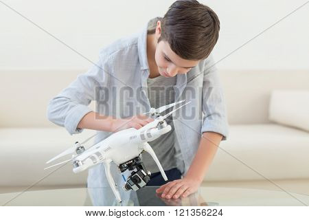 Pretty male teenager is using a drone