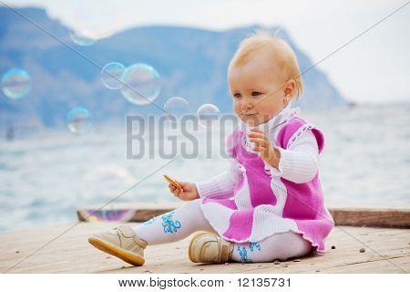 Portrait of little cute baby girl looking on soap bubbles on berth near sea